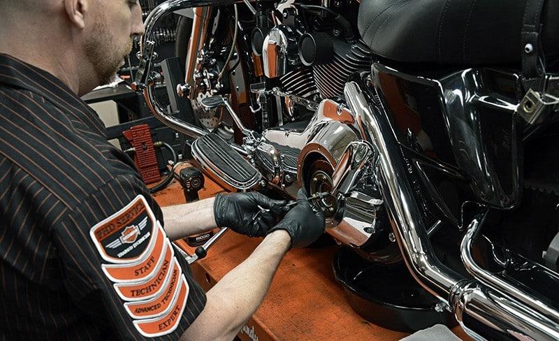 Técnico autorizado Harley-Davidson realizando ajuste em embreagem de motocicleta da marca